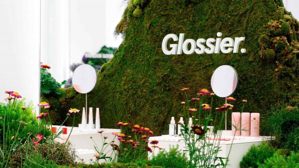Diseño de vitrina para la marca de cosméticos Glossier, utilizando musgo, gramineas y flores.