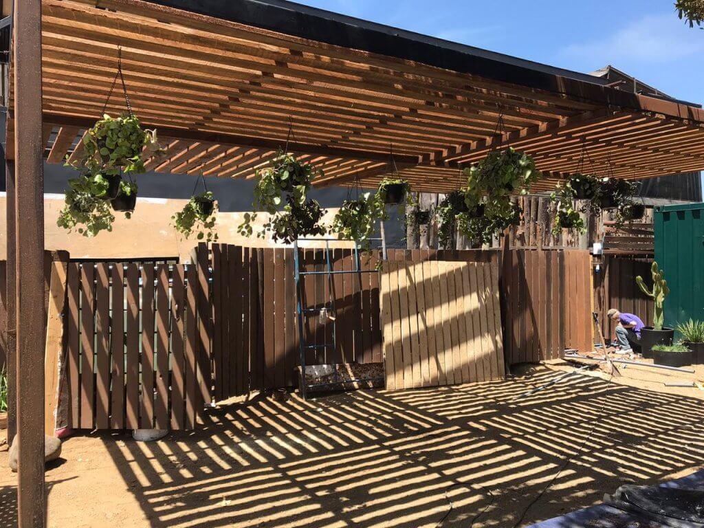 Diseño de terraza zona de transición entre el jardín boscoso y playero. Se utiliza la estructura de madera para colgar maceteros con plantas colgantes, a diferentes alturas.