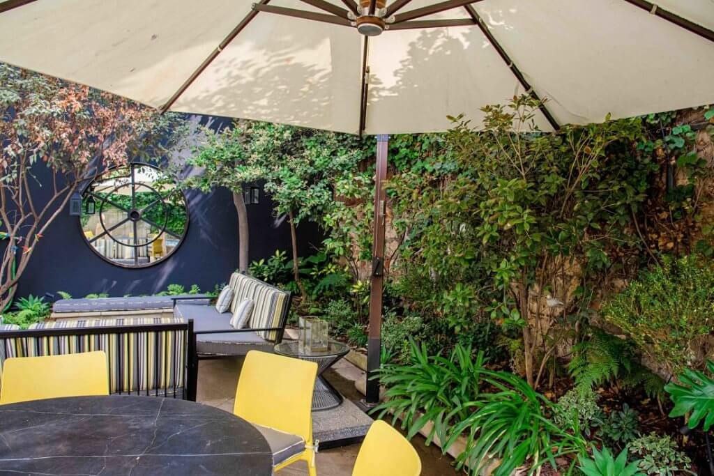 Jardín de bajo mantenimiento, sin uso de pasto. Terraza con pastelones de piedra y macizos perimetrales.