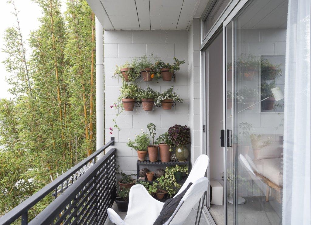 Maceteros y jardineras de greda pegados a la pared del fondo, de una terraza de departamento.