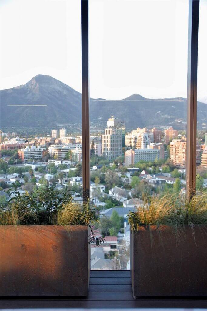 Jardineras de metal oxidado con mezcla de Stipa caudata y Verbena bonaerense. Atrás de las jardineras, una vista desde el piso 15 hacia la comuna de Vitacura, Santiago.