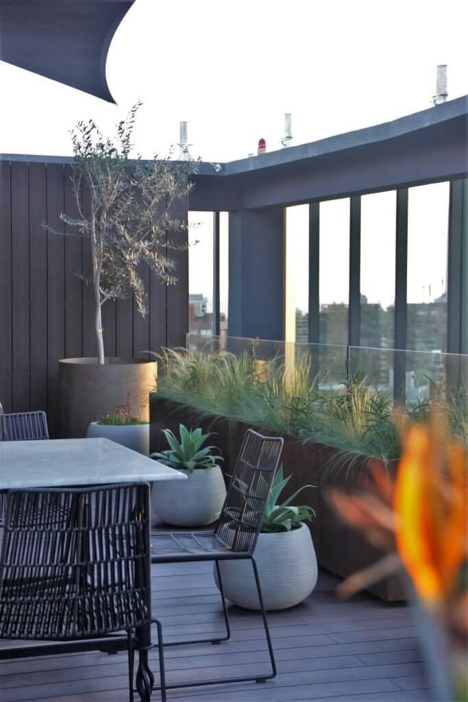 Detalle a jardineras y maceteros redondos de la zona del living.